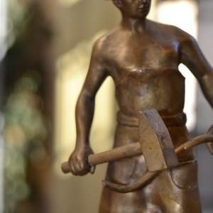 Bronzová soška kováře s kovadlinou